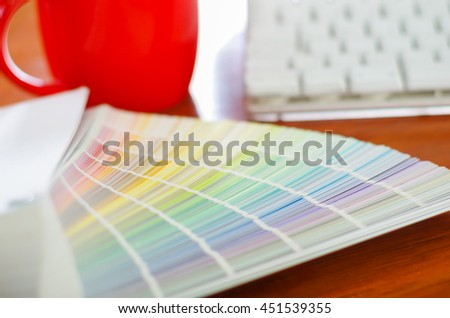 Closeup large palette colormap spread out in front of white computer keyboard and red coffee mug sitting on wooden desk, designer concept