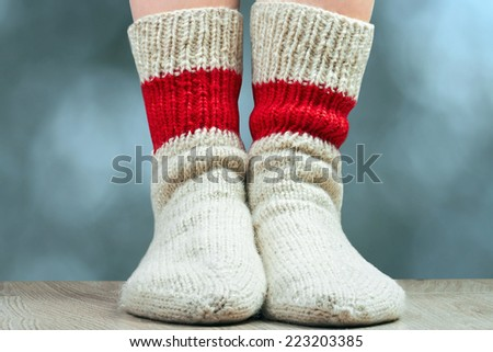 closeup  legs with pair wool knitted socks. blue  background  behind - stock photo