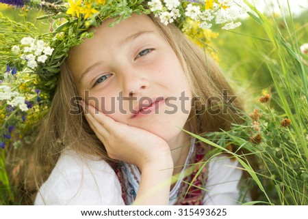 Closeup little girl in wreath of flowers lay in meadow - stock photo