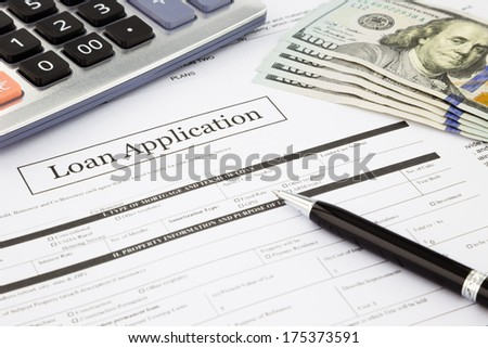 closeup loan application form and dollar banknotes, business and finance concept and idea - stock photo