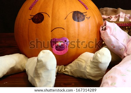 Closeup look at a pumpkin baby with pacifier - stock photo