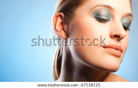 Closeup look of gorgeous young woman with blue makeup on blue background - stock photo