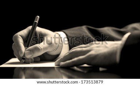 Closeup low angle perspective of a businessman in a suit signing a document with a fountain pen as he closes a business deal or finalises a contract or agreement - stock photo