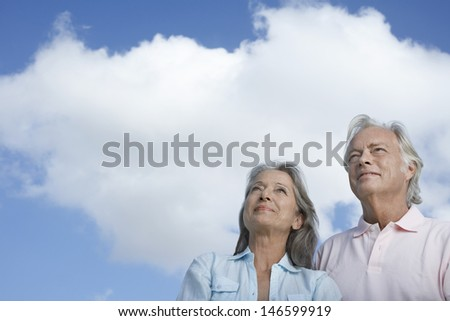 Closeup low angle view of a mature couple looking up against sky - stock photo