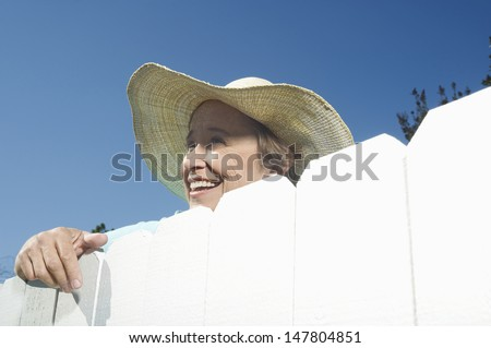 Closeup low angle view of a smiling woman peering over garden fence - stock photo