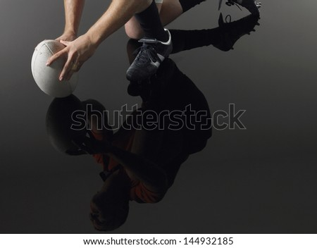 Closeup low section and reflection of a rugby player kneeling on one knee with ball - stock photo