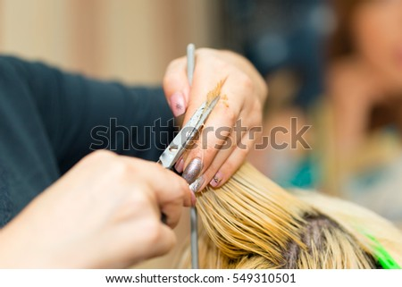 Closeup macro shot image of hairstylist hairdresser cutting customer woman hair in salon with scissors and comb, look from behind back side