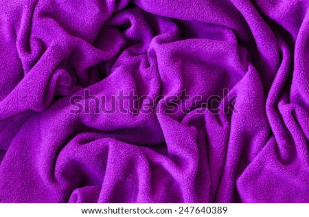 Closeup macro texture of pink violet purple fleece fabric, clothing background with wrinkles and folds - stock photo