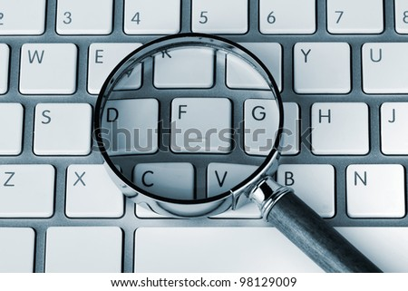 Closeup Magnifying glass on an white keyboard in blue key - stock photo