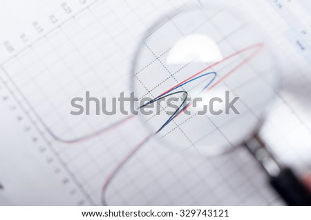 Closeup magnifying glass over paper with red and blue graph visible. - stock photo