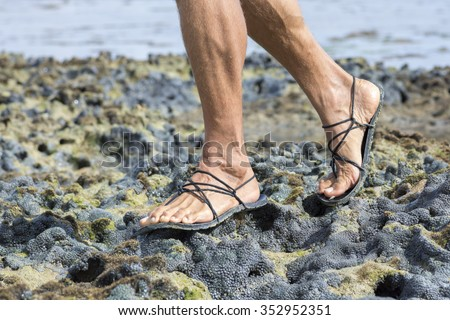 Closeup male feet wearing primitive black sandals walking over living coral reef at low tide - stock photo