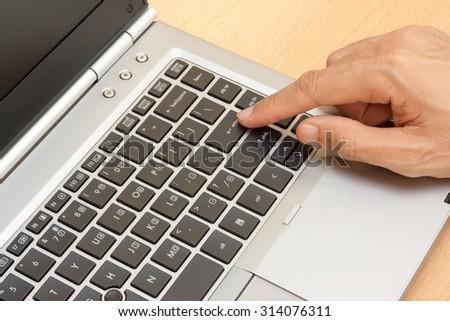 closeup male hand typing on laptop keyboard - stock photo