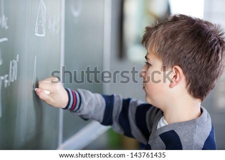 Closeup male student writing on chalkboard in classroom - stock photo
