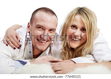 Closeup man and woman in white shirts lie embracing on the white shaggy carpet and both laugh.