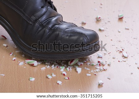 Closeup man's black dress shoe stepping onto and shattering Christmas candy cane on wood floor - stock photo