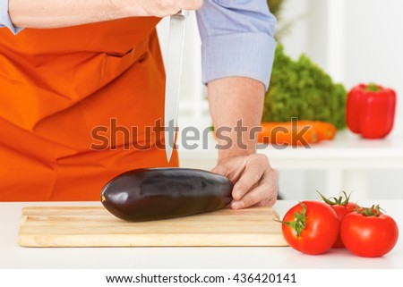 Closeup man's hands cutting vegetables on a work surface in a kitchen. - stock photo