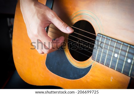 Closeup man's hands playing acoustic guitar with dark vignette. - stock photo