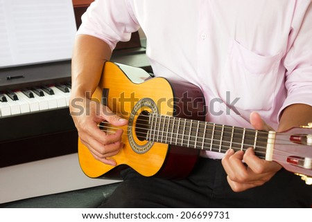 Closeup man's hands playing classic guitar with piano background. - stock photo