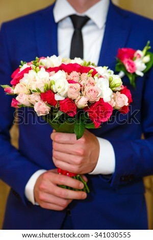 Closeup Man the groom in the blue wedding suit, bridal bouquet with white and red roses in hands, flowers boutonniere on his lapel - stock photo