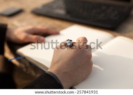 Closeup man writing notes in personal notebook with right hand. - stock photo