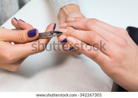 Closeup manicure nail technician worker perfoming procedure for hand care in beauty salon. Cuticle clipping, cutting skins manicure treatment with the fourth finger client. - stock photo