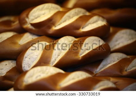 Closeup many fresh baked whole long loaves wheat bread with crunchy crusts arranged in pile on seamless background, horizontal picture - stock photo