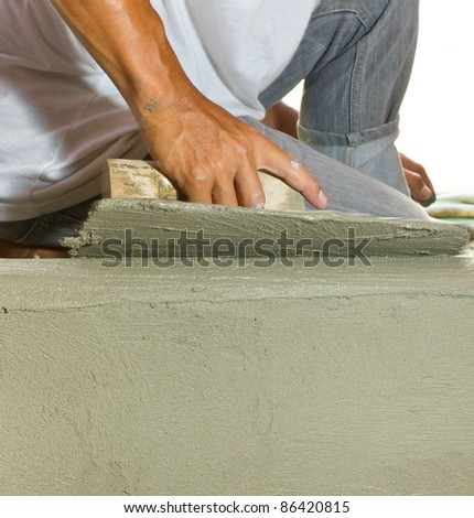 Closeup mason  hand spreading fresh concrete mix with trowel - stock photo