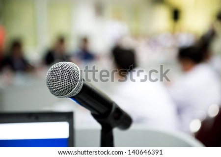 Closeup microphone in conference room with blur person. - stock photo