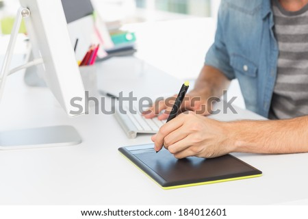 Closeup mid section of a casual male photo editor using graphics tablet in a bright office - stock photo