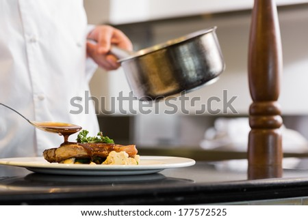 Closeup mid section of a chef garnishing food in the kitchen - stock photo