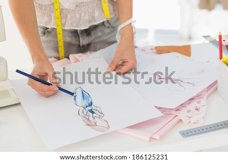 Closeup mid section of a female fashion designer working on her designs in the studio - stock photo