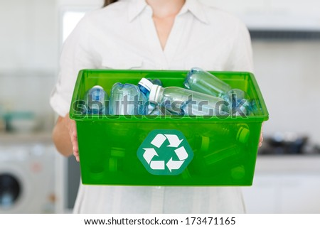 Closeup mid section of a woman carrying box with recycling symbol in the house