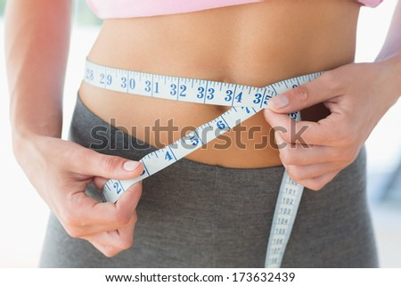 Closeup mid section of a woman measuring waist in fitness studio