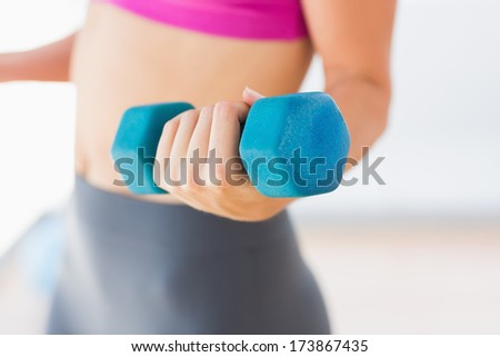 Closeup mid section of a young woman lifting dumbbell weight in a bright gym - stock photo