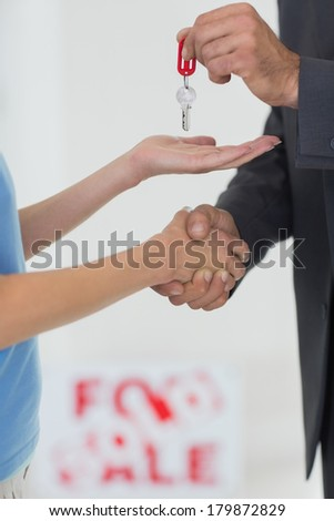 Closeup mid section of handshake and passing house key - stock photo