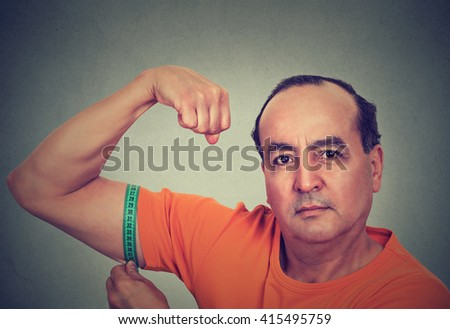 Closeup middle aged man flexing his muscle measuring his biceps isolated on gray wall background. Fitness goal achievement result concept  - stock photo