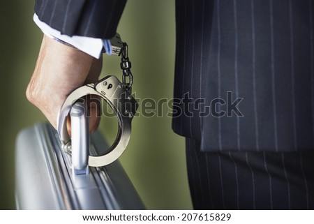 Closeup midsection of a businessman handcuffed to briefcase against green background - stock photo