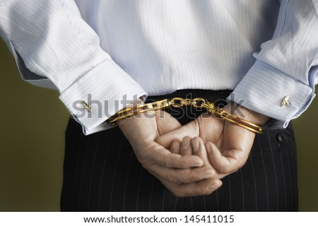 Closeup midsection of a businessman with hands cuffed behind back against green background - stock photo