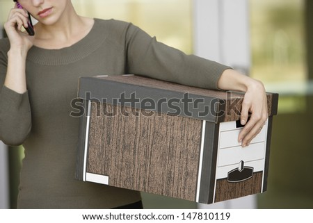 Closeup midsection of a businesswoman using mobile phone while carrying moving box - stock photo