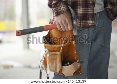Closeup midsection of a male construction worker wearing tool belt - stock photo