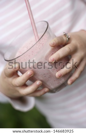 Closeup midsection of little girl holding smoothie glass - stock photo