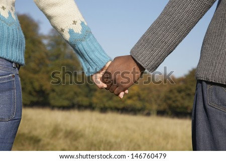 Closeup midsection of multiethnic young couple holding hands in field - stock photo