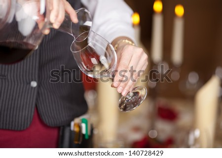 Closeup midsection of waitress pouring red wine in wineglass from decanter