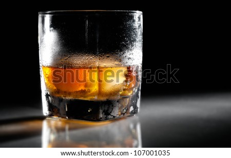 Closeup misted cold glass of whiskey in backlight - stock photo
