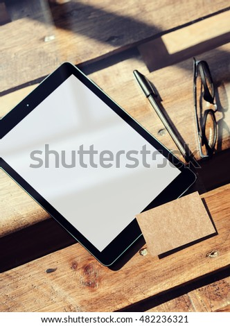 Closeup Modern Tablet Blank White Screen,Glasses Wood Table Inside Interior Coworking Loft.Empty Mockup Design Kraft Paper Business Card Corporate Message Background.Mock Up Private Objects Text