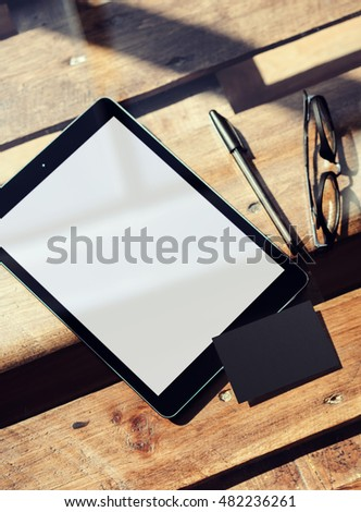 Closeup Modern Tablet Blank White Screen,Glasses Wood Table Inside Interior Coworking Studio.Empty Mockup Design Black Business Card Corporate Message Background.Mock Up Private Objects Text.Vertical