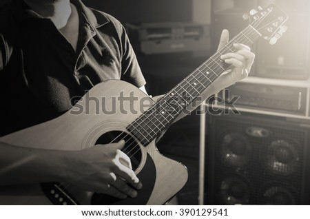 Closeup musician playing the guitar on band background with spot light, musical concept