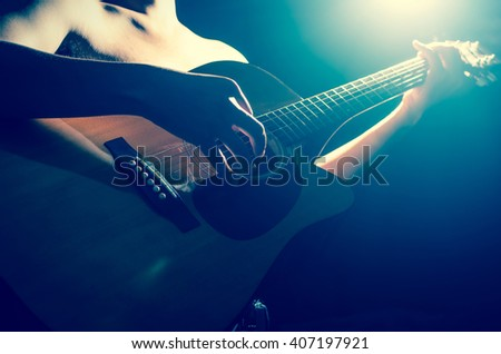 Closeup musician playing the guitar on spot light background, musical concept - stock photo