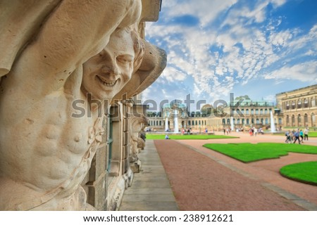 Closeup naked faunus smiling statue crop with fountain and garden at Zwinger palace in Dresden, Germany  - stock photo