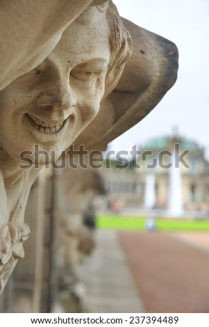Closeup naked satyr smiling statue crop with fountain and garden at Zwinger palace in Dresden, Germany - stock photo